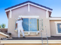Parramatta painter working on the exterior of a property with white paint